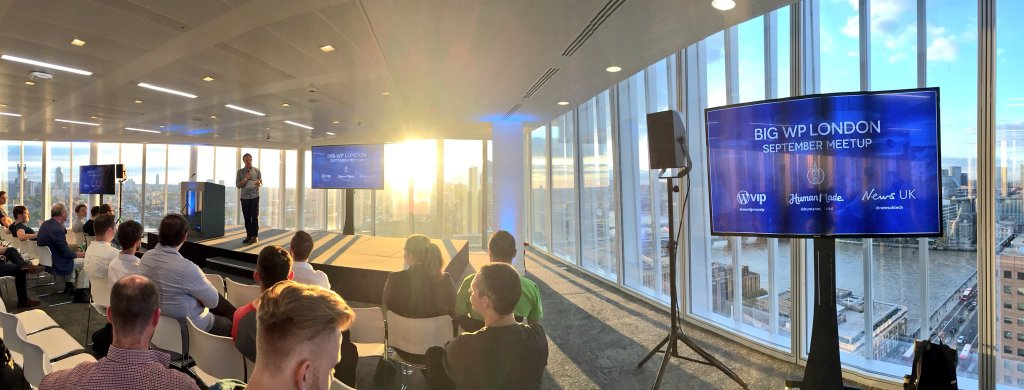 Photo from Big WP London meetup, high up in an office block, looking at a stage, with the sunsetting behind.