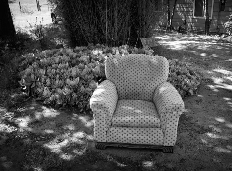 A stuffed chair by the side of the road