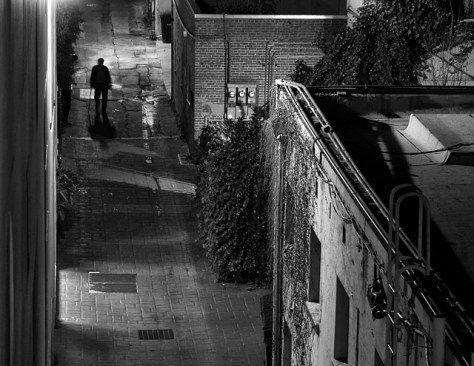 Night scene of man with cane in alley