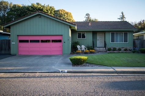 Pink garage door on well kept suburban home