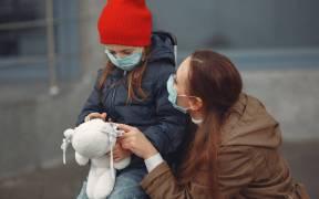Mujer y niña en la calle con mascarillas