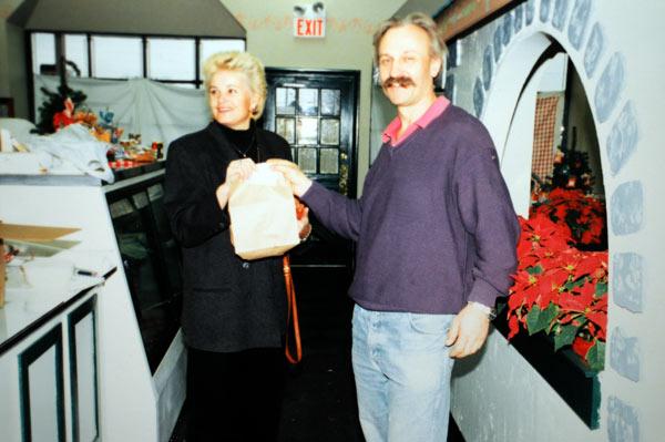 Michael Greipel hands Ingeborg Chandler, our first customer, her items.