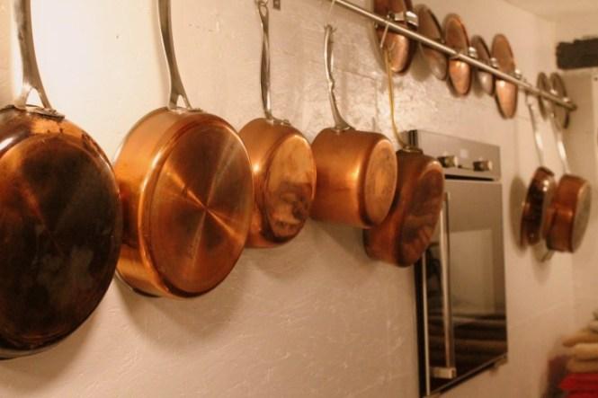 Brugt kobbertøj hænger og er klar til brug.