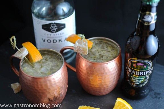 Orange Moscow Mule in Copper Mugs with candied ginger and orange slices on cocktail picks