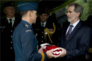 Brigadier General Alain Pelletier, Senior Representative of the Canadian Armed Forces, presents David Carey, nephew of Flight Sergeant John Joseph Carey, the Canadian flag, which had adorned F/Sgt Carey's coffin during his funeral at the Rheinberg Commonwealth War Graves Cemetery, Germany on July 9, 2014.  Image by: Corporal Pamela Turney.