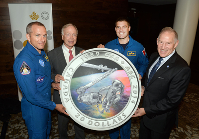 From left to right: Astronaut David Saint-Jacques, Royal Canadian Mint Board of Directors member John Bell, astronaut Jeremy Hansen and Canadian Space Agency (CSA) President Walter Natynczyk unveil a silver collector coin celebrating the 25th anniversary of the CSA on September 30 at the 2014 International Astronautics Congress in Toronto. (CNW Group/Royal Canadian Mint)