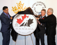 From left: The Honourable Bal Gosal, Minister of State (Sport), Mr. Marc Brûlé, Interim President and CEO of the Royal Canadian Mint and Mr. Tom Renney, President and CEO of Hockey Canada unveil a new silver collector coin to celebrate the 100th anniversary of Hockey Canada at the Fairmont Chateau Laurier in Ottawa, Ontario. (CNW Group/Royal Canadian Mint)
