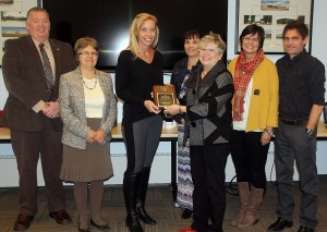 Dorothy Burns (2nd from left) & Sharon Malec (3rdfrom right) present the award to Superintendent John Bailey, Board Chair Christine Pretty, Senator Riley's Tracey McKinnon, and Spitzee's Brooke MacNeill & Mark Traber