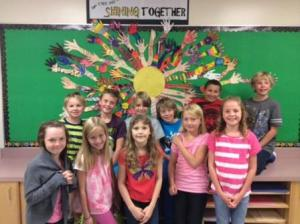 """Dr. Morris Gibson students in front of the school's """"Shining Together"""" theme poster"""