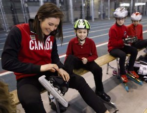 Long track speedskater Anastasia Bucsis, left, helps Jackson Jones, of the Calgary Speed Skating Club, with his skate after Bucsis was named to Canada's team heading to the 2014 Sochi Olympics at a news conference in Calgary, Alta., Wednesday, Jan. 22, 2014.THE CANADIAN PRESS/Jeff McIntosh