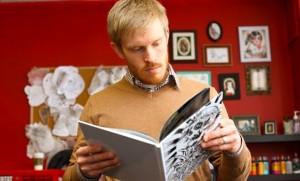 PhD student Alec Falkenham looks through tattoo designs at Halifax's Brass Anchor tattoo parlour. (Bruce Bottomley photos)