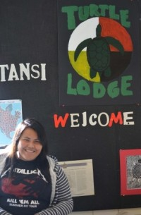 Grade 12 Oilfields student Tashena Daniels stands in front of sign she designed for the Turtle Lodge