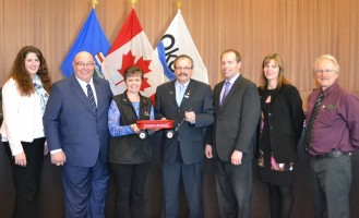 Alberta's Promise presents Mayor Bill Robertson (fourth from left) and the Town of Okotoks with their Little Red Wagon.