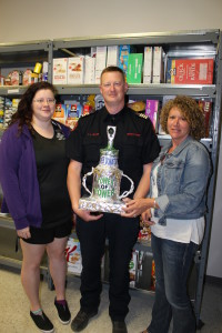 Town of High River lifeguard Kristi Kabeary and Deputy Fire Chief Trevor Allan receive a trophy from Kate Tymstra in recognition of winning a staff challenge to help the local Food Bank.