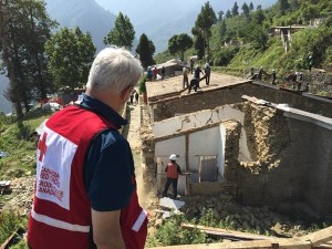 Canadian aid worker Dr. David Allison watches as the original Dhunche hospital is being demolished after it was significantly damaged in the earthquake. The Canadian Red Cross field hospital is set up nearby. /Photo courtesy: Diana Coulter