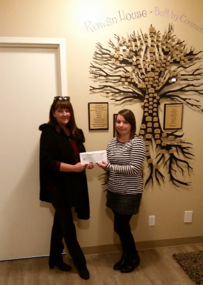 Jackie Berglund, owner of Snowflakes & Blossoms presents a cheque to Rowan House