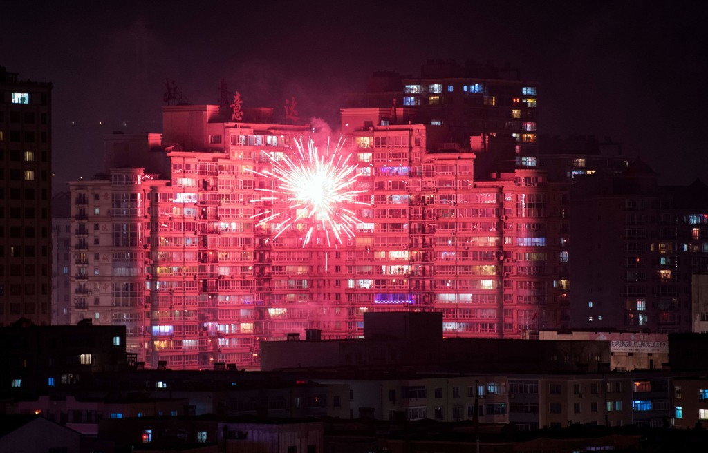 Fireworks illuminate buildings of the Chinese border town of Dandong as people celebrate the eve of the Lunar New Year. (Getty)