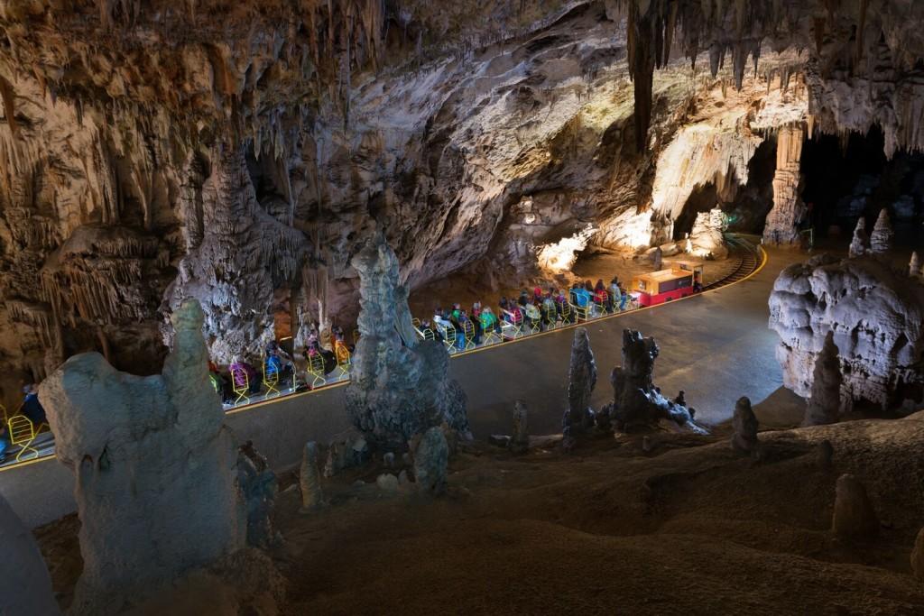 A train carries tourists on a tour of Postojna Cave. Image via Postojna Cave Park.