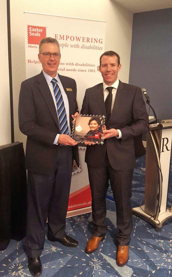 Easter Seals Alberta Board of Director Bradley Wamboldt presents the Honourable Norman Kwong Award to Foothills MP John Barlow