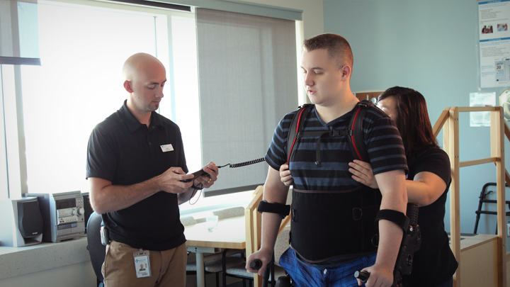 Physical Therapist Kyle McIntosh, left, and Olivia Dong, Clinical Leader, Physical Therapy, assist Alex, who recently suffered a spinal cord injury, as he stands up and walks in an exoskeleton rehabilitation device.