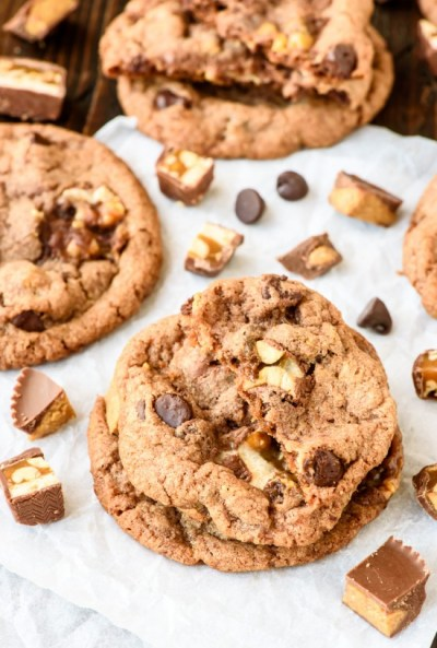 Soft-and-Chewy-Peanut-Butter-Snickers-Cookies.-Reeses-peanut-butter-cups-and-Snickers-bars-baked-into-soft-chewy-cookies-that-are-loaded-with-chocoalte-chips-Perfect-for-leftover-candy-550x815