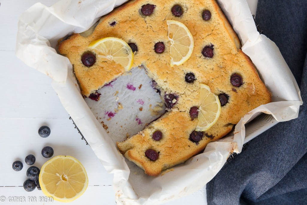 Lemon Blueberry Snack Cake - Simple cake in a pan with fresh blueberries and lemon for zest. Delightful! | gatherforbread.com