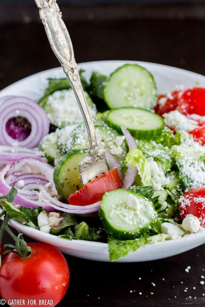 Easy Mediterranean Salad - Easy Greek style salad with homemade dressing recipe. Topped with tomato, cucumber, romaine and Feta. Light on calories for your diet. Gluten free.