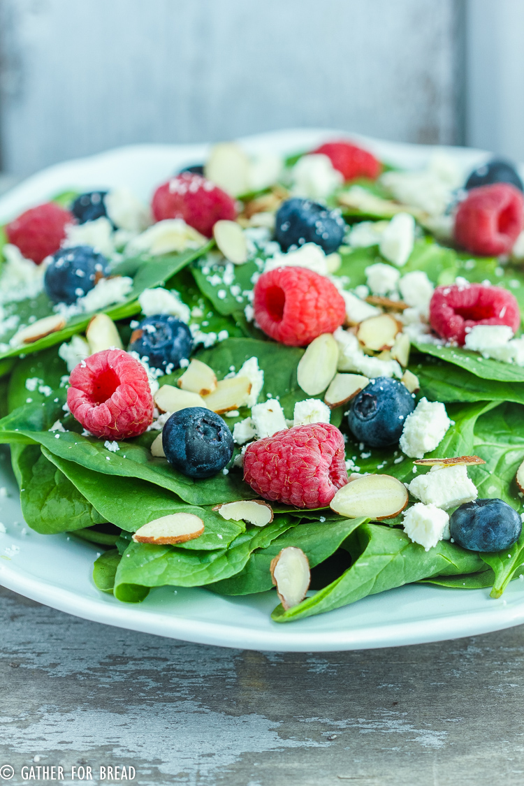 Berry Spinach Salad with Homemade Raspberry Vinaigrette - Green spinach salad recipe topped with berries and the BEST homemade raspberry vinaigrette; feta cheese, almonds with raspberries, blueberries.