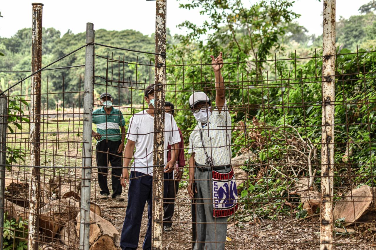 Los agricultores deben pasar sus cargas por encima del cerco metálico que ha instalado la Central Hidroeléctrica de Juayúa. Pedro Rodríguez, líder indígena, se hirió la mano tratando de pasar un trozo de madera. Foto/ Émerson Flores.