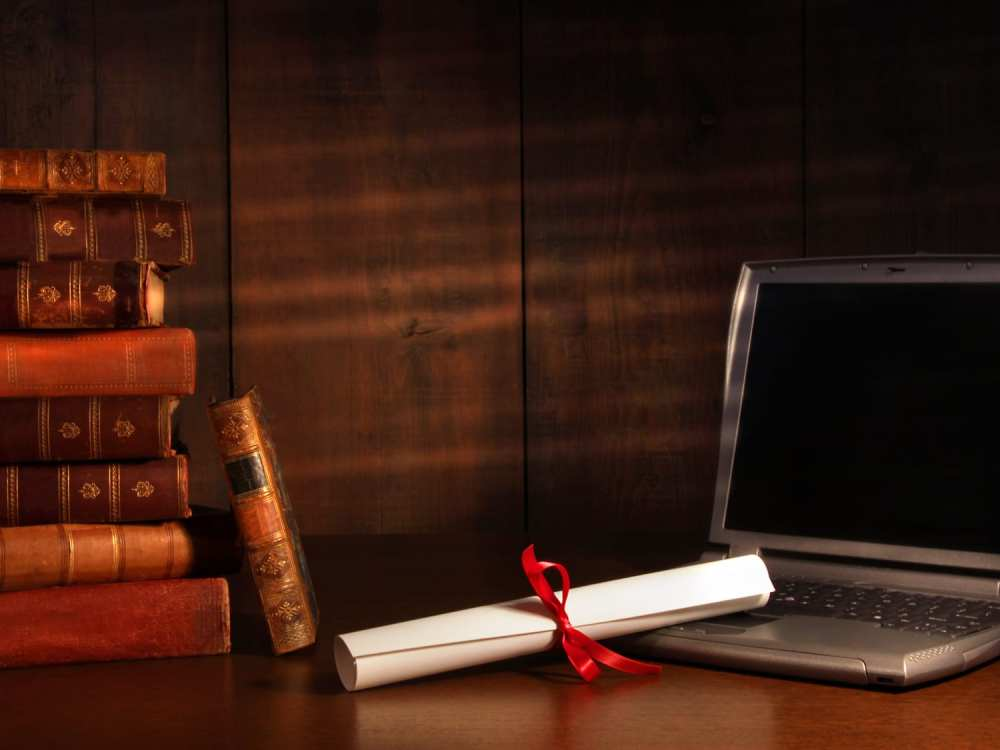 Antique books, diploma with laptop on desk