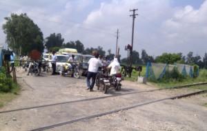 ट्रेन आने से आधा घंटा पहले बंद हुये फाटक से गुजरते लोग।