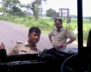 थाना बिनावर की सीमा पर दबंग स्टाइल में खड़े थानाध्यक्ष और बस को रोकने को शीशे में घुसने का प्रयास करता सिपाही।