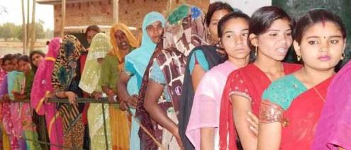 मतदान केंद्र पर वोट डालने के इंतजार में लाइन में खड़ी महिलाएं