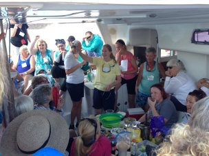April 18 Yours truly leading the raffle on S/V Satisfaction with Kathy and Charity helping, photo by Heidi Hackler