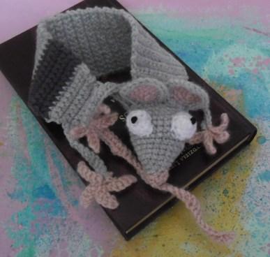 Zakładka do książki w kształcie szczura z wyłupiastymi oczami zwinięta na brązowej książce.