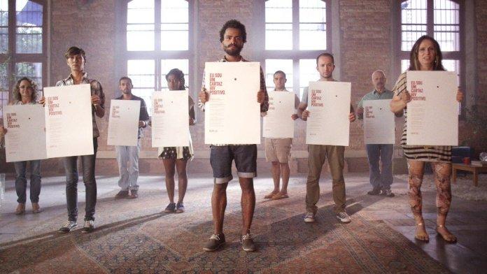 Voluntários seguram cartazes de campanha contra o preconceito a pessoas com HIV