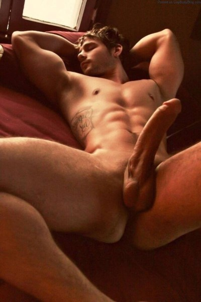 Quinn Christopher Jaxon laying back with his very large cock on display