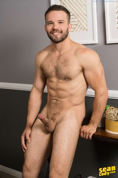hairy and handsome hunk leaning on a table with his hard uncut cock on display