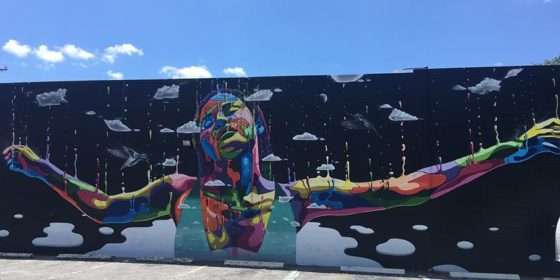 A rainbow figure stretches out their arms in a St Pete mural