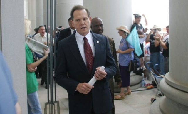 MONTGOMERY, AL ? AUGUST 21: Alabama Supreme Court Chief Justice Roy Moore walks back into the state Judicial Building after addressing supporters August 21, 2003 in Montgomery, Alabama. The eight other justices today overruled Moore?s defiance of a federal court order to remove a 5,300 lb granite monument of the Ten Commandments that is exhibited in the Judicial Building. Moore defied a deadline to get rid of the monument by midnight today. The U.S. Supreme Court declined to consider the issue Wednesday. (Photo by Gary Tramontina/Getty Images)