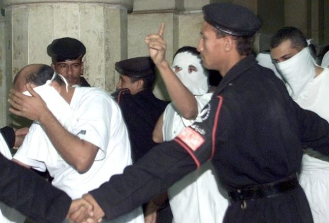 CAIRO, EGYPT: Egyptians with their faces covered, charged with engaging in homosexual activities and scorning Islam, enter a Cairo court under the protection of security men 14 November 2001. One of the 52 men was sentenced to five years in prison and several to three years at the end of their trial. The men were arrested in May following a party on a Nile riverboat. AFP PHOTO/Marwan NAAMANI (Photo credit should read MARWAN NAAMANI/AFP/Getty Images)
