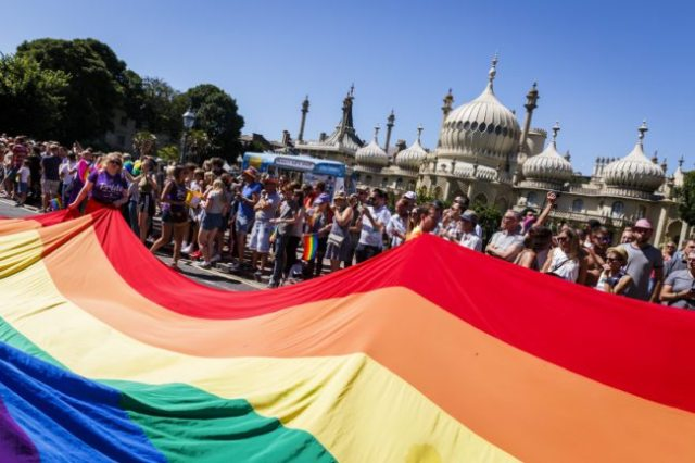 BRIGHTON, ENGLAND - AUGUST 06: The rainbow flag is carried through the streets at the Brighton Pride Parade on August 6, 2016 in Brighton, England. (Photo by Tristan Fewings/Getty Images)