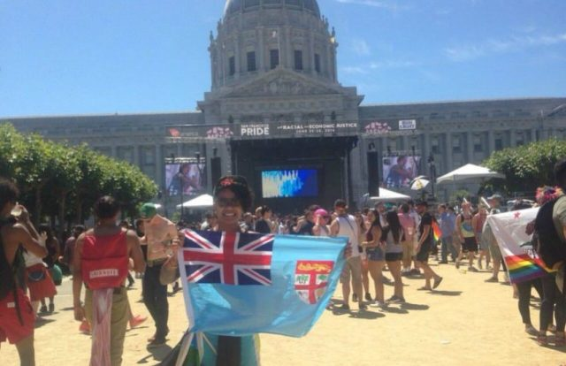 Woman holds Fijian flag at concert