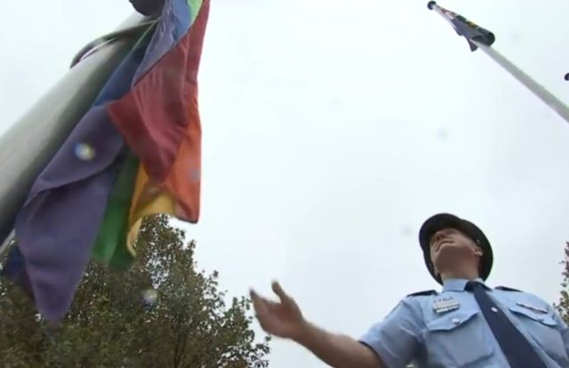 A police officer watches as the rainbow flag goes up a flag pole