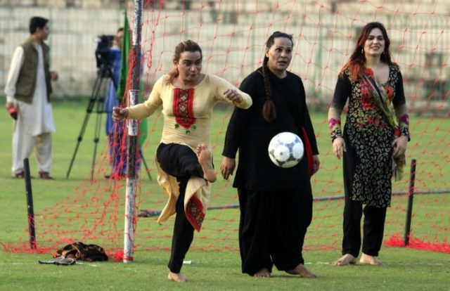 a woman kicking a soccer ball as two other women look on