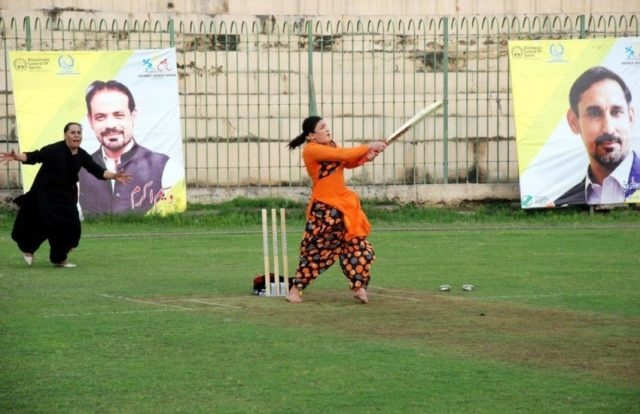 A woman at a cricket wicket hitting a ball with a cricket bat, she's wearing orange