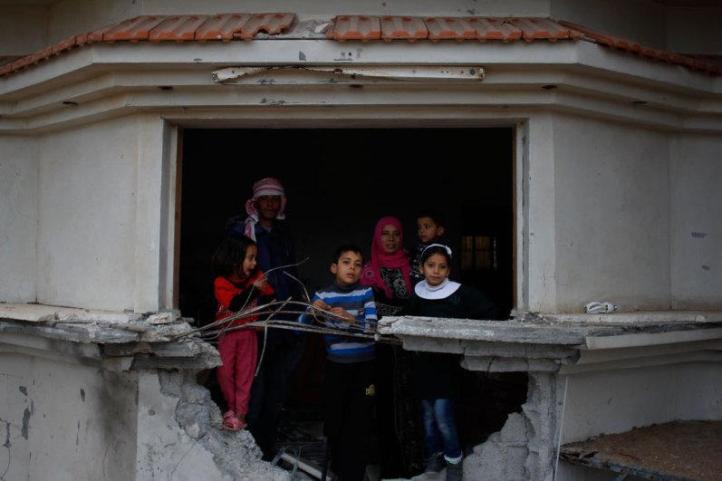 Family in the window of their bombed out home