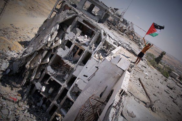 Boy with the flag of Palestine and peace sign on top a bombed out apartment building