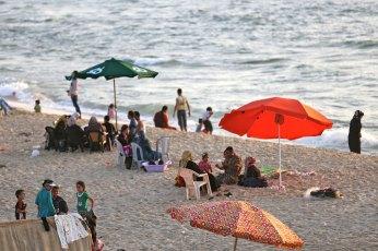 Families under umbrellas on Gaza beach