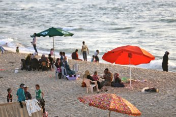 Families under umbrellas on Gaza beach